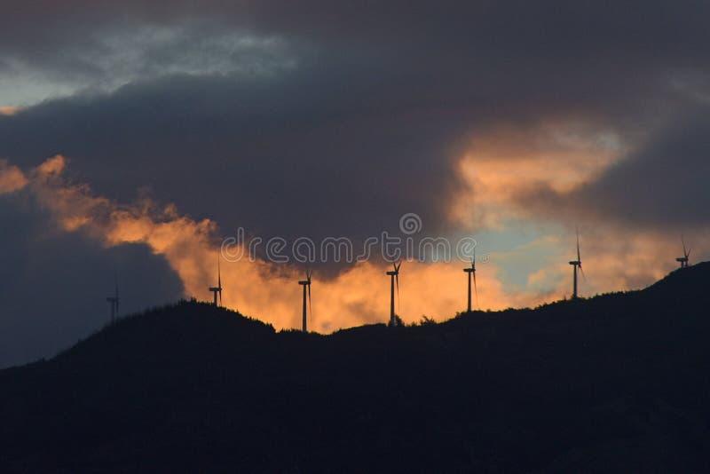 Στρόβιλοι αιολικής ενέργειας πάνω από τα βουνά στο σούρουπο στοκ εικόνες