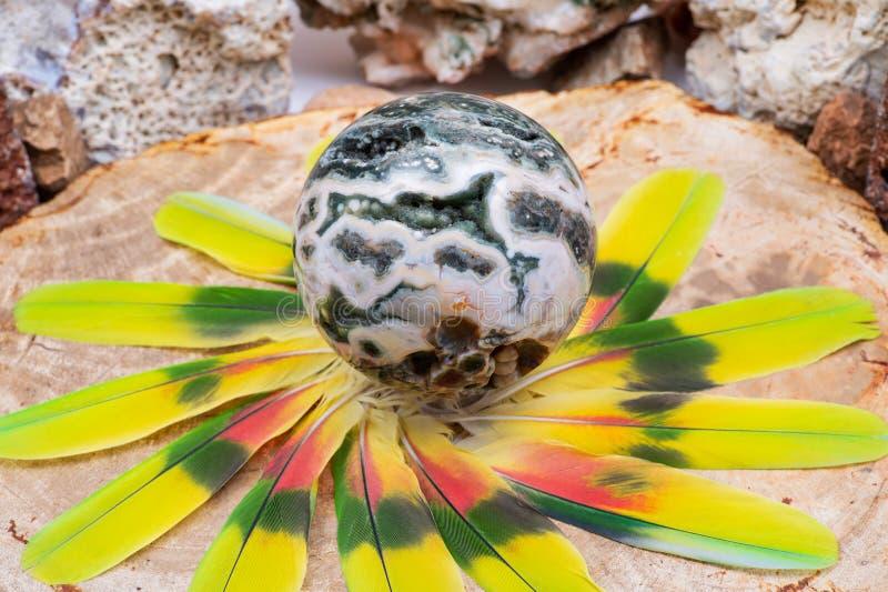 Σφαιρική ωκεάνια σφαίρα ιασπίδων με κρυσταλλωμένος vugs από τη Μαδαγασκάρη στη μέση ενός κύκλου φιαγμένου από ζωηρόχρωμα φτερά στοκ φωτογραφίες