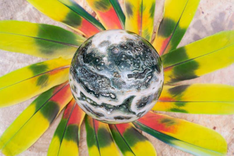 Σφαιρική ωκεάνια σφαίρα ιασπίδων με κρυσταλλωμένος vugs από τη Μαδαγασκάρη στη μέση ενός κύκλου φιαγμένου από ζωηρόχρωμα φτερά στοκ εικόνες