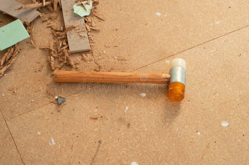 Σφυρί για τη φυλλόμορφα εγκατάσταση και τα υπολείμματα του φύλλου πλαστικού φετών στο πάτωμα στοκ εικόνα με δικαίωμα ελεύθερης χρήσης