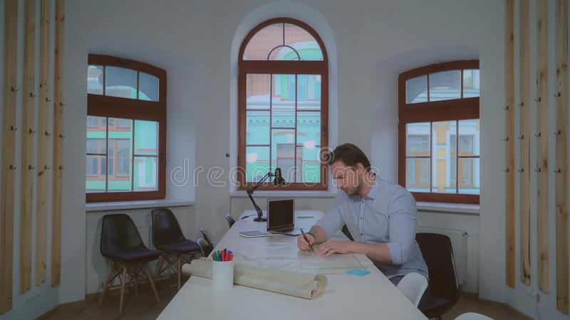 Σχεδιαστής που στρέφεται στο αρχιτεκτονικό σχέδιο στοκ φωτογραφία