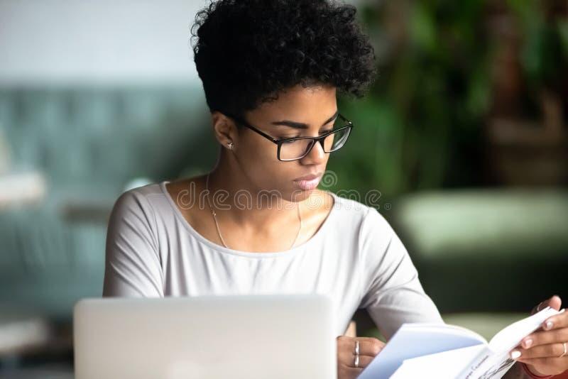 Συγκεντρωμένη αφρικανική όμορφη γυναίκα που μελετά διαβάζοντας ένα βιβλίο στοκ εικόνα με δικαίωμα ελεύθερης χρήσης