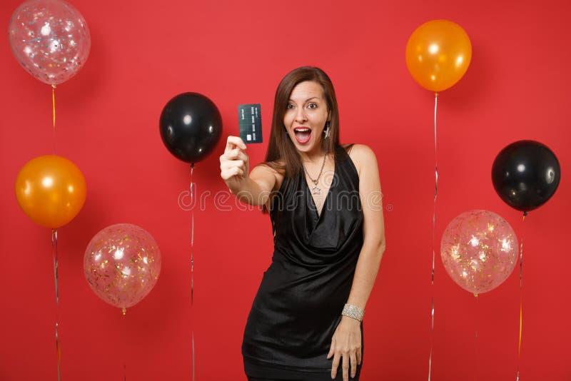 Συγκινημένη νέα γυναίκα σε λίγο μαύρο εορτασμό φορεμάτων, που παρουσιάζει πιστωτική κάρτα στη κάμερα στα κόκκινα μπαλόνια αέρα υπ στοκ φωτογραφία με δικαίωμα ελεύθερης χρήσης