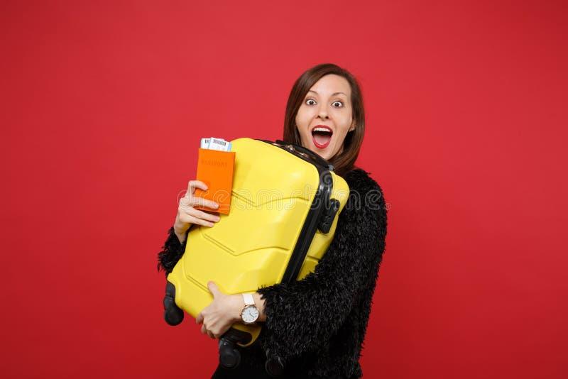 Συγκινημένη νέα γυναίκα στο μαύρο πουλόβερ γουνών με την ανοιγμένη βαλίτσα στοματικής εκμετάλλευσης, εισιτήριο περασμάτων τροφής  στοκ εικόνες