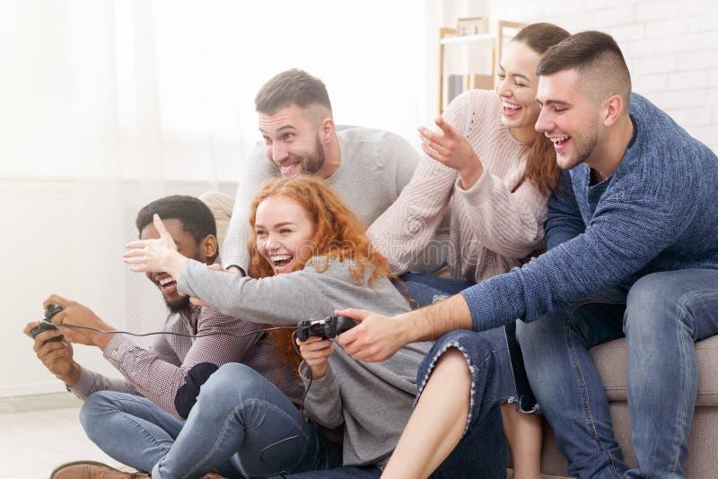 Συγκινημένοι φίλοι που παίζουν τα τηλεοπτικά παιχνίδια μαζί, έχοντας τη διασκέδαση στοκ φωτογραφία με δικαίωμα ελεύθερης χρήσης