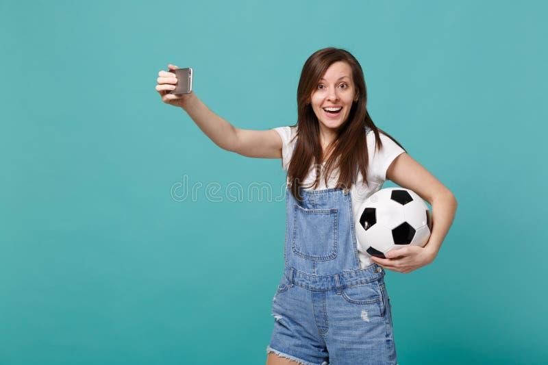 Συγκινημένος νέος οπαδός ποδοσφαίρου γυναικών με τη σφαίρα ποδοσφαίρου που κάνει selfie τον πυροβολισμό στο κινητό τηλέφωνο που α στοκ φωτογραφία με δικαίωμα ελεύθερης χρήσης