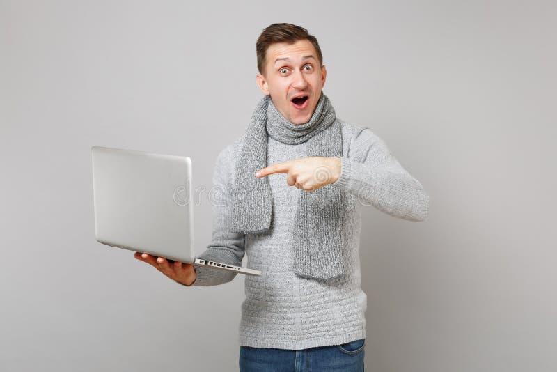 Συγκινημένος νεαρός άνδρας στο γκρίζο πουλόβερ, μαντίλι με το ανοιγμένο στόμα που δείχνει το αντίχειρα στον υπολογιστή PC lap-top στοκ εικόνες
