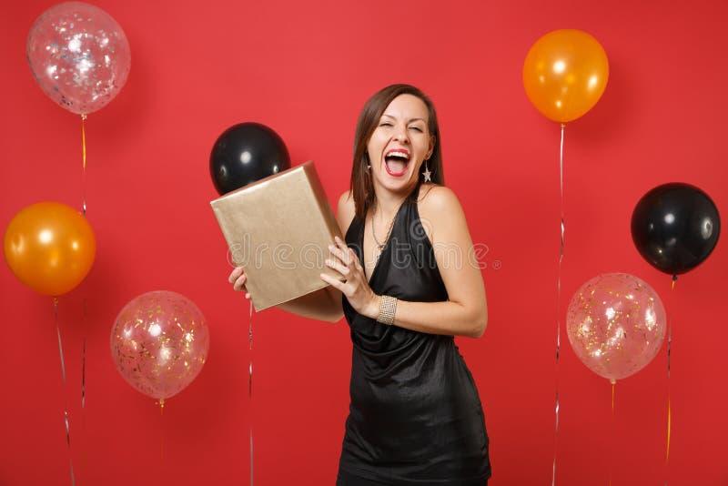 Συγκινημένο ευτυχές κορίτσι σε λίγο μαύρο χρυσό κιβώτιο λαβής εορτασμού φορεμάτων με το δώρο παρόν στο φωτεινό κόκκινο αέρα υποβά στοκ εικόνες με δικαίωμα ελεύθερης χρήσης
