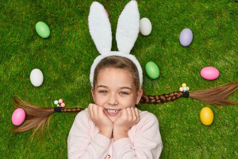 Συγκινημένο κορίτσι που βρίσκεται στη χλόη κοντά στα αυγά Πάσχας στοκ εικόνες