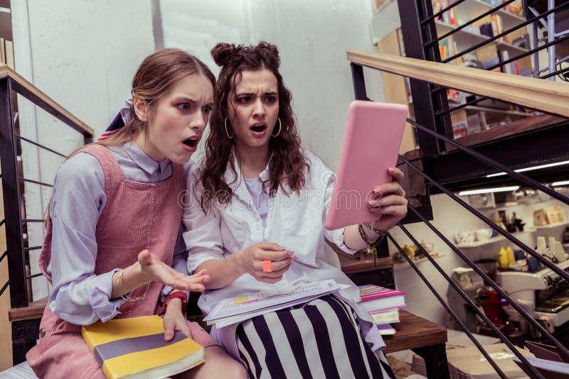 Συγκλονισμένα εκφραστικά κορίτσια που κοιτάζουν στην οθόνη ταμπλετών με τα ανοιγμένα στόματα στοκ εικόνα με δικαίωμα ελεύθερης χρήσης