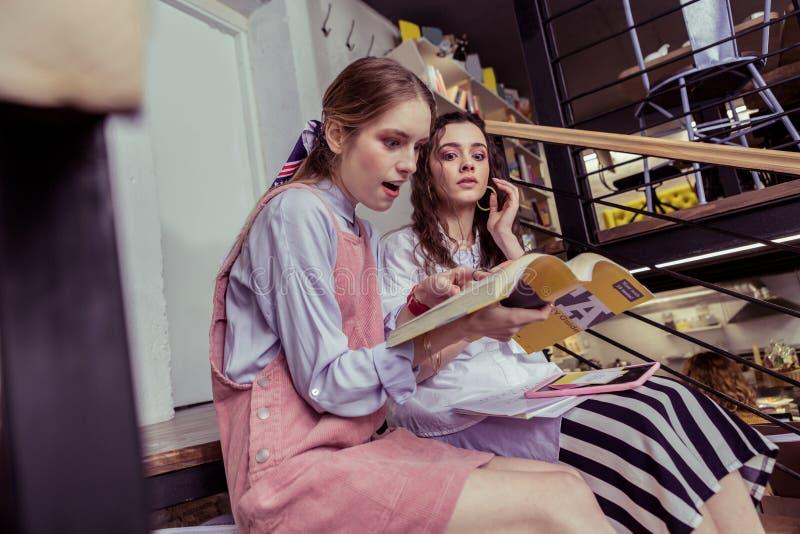 Συγκλονισμένα ελαφρύς-μαλλιαρά κορίτσια που κοιτάζουν στο κείμενο στο βιβλίο με το ανοιγμένο στόμα στοκ φωτογραφίες