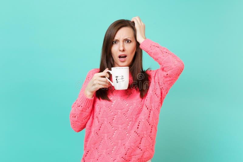 Συγκλονισμένη νέα γυναίκα στο πλεκτό ρόδινο πουλόβερ που βάζει το χέρι στο επικεφαλής φλιτζάνι του καφέ εκμετάλλευσης ή το τσάι π στοκ φωτογραφίες με δικαίωμα ελεύθερης χρήσης