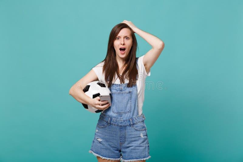 Συγκλονισμένος νευρικός οπαδός ποδοσφαίρου γυναικών με τη σφαίρα ποδοσφαίρου που χρησιμοποιεί το κινητό τηλέφωνο, που βάζει το χέ στοκ εικόνες με δικαίωμα ελεύθερης χρήσης