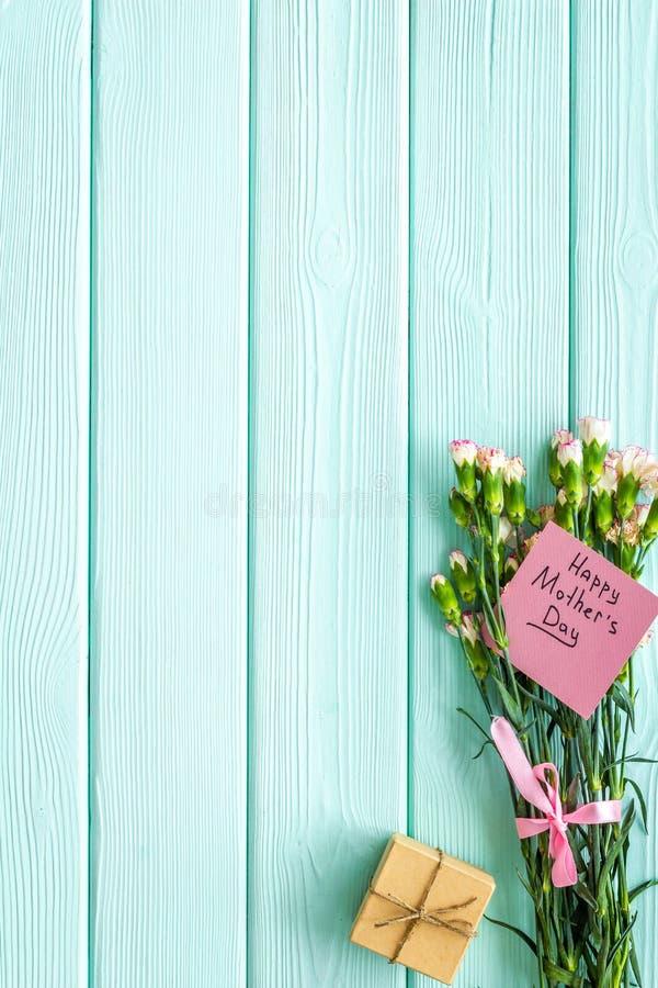 Συγχαρητήρια ημέρας μητέρας Γαρίφαλα και κιβώτιο δώρων στο μπλε τυρκουάζ ξύλινο διάστημα αντιγράφων άποψης υποβάθρου τοπ στοκ φωτογραφία με δικαίωμα ελεύθερης χρήσης