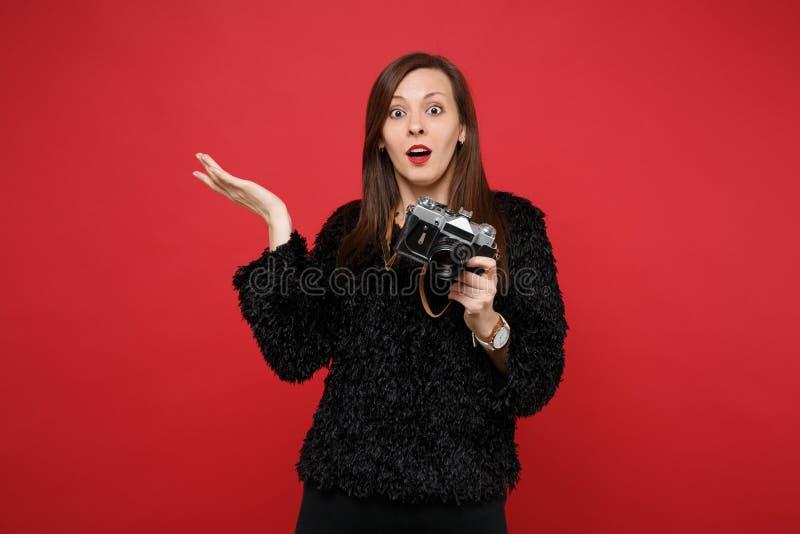 Συγχυσμένη νέα γυναίκα στο μαύρο χέρι διάδοσης πουλόβερ γουνών, που κρατά την αναδρομική εκλεκτής ποιότητας κάμερα φωτογραφιών απ στοκ εικόνες