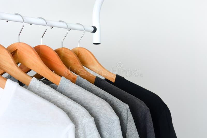 Συλλογή της μαύρης, γκρίζας και άσπρης ένωσης χρώματος στην ξύλινη κρεμάστρα ενδυμάτων στο ντουλάπι ή το ντύνοντας ράφι στοκ φωτογραφία με δικαίωμα ελεύθερης χρήσης