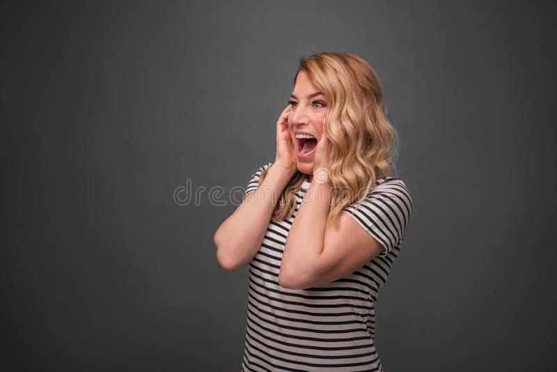 Συναισθηματικές ξανθές κραυγές Εκφοβισμένη τεντώνοντας στάση κραυγής γυναικών σε ένα γκρίζο υπόβαθρο στοκ φωτογραφία