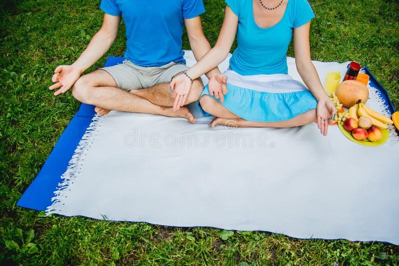 Συνεδρίαση ανδρών και γυναικών ζεύγους στο λιβάδι με την πράσινη χλόη στη θέση Lotus Meditate εν την ειρήνη και την ελευθερία στοκ εικόνα