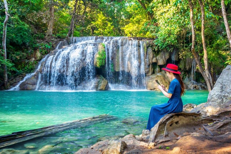 Συνεδρίαση γυναικών στον καταρράκτη Erawan στην Ταϊλάνδη Όμορφος καταρράκτης με τη σμαραγδένια λίμνη στη φύση στοκ εικόνες