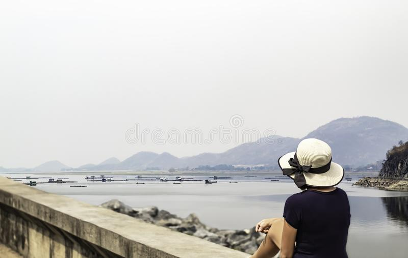 Συνεδρίαση γυναικών στο υπόβαθρο τσιμεντένιων πλακών η να επιπλεύσει συνόλων καλλιέργεια ψαριών στο νερό και τα βουνά στο φράγμα  στοκ εικόνες με δικαίωμα ελεύθερης χρήσης