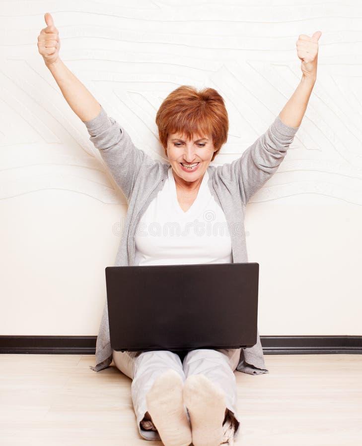 Συνεδρίαση γυναικών στο πάτωμα με το lap-top στοκ φωτογραφία