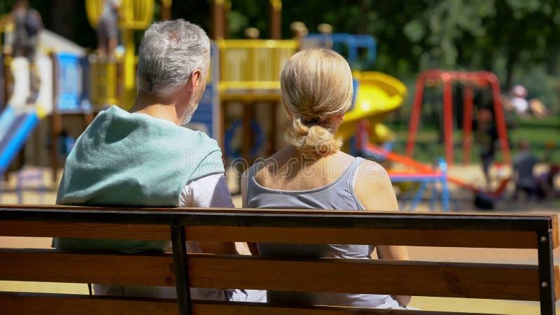 Συνταξιούχοι άνδρας και γυναίκα στον πάγκο στα προσέχοντας εγγόνια πάρκων, ευτυχείς μνήμες στοκ φωτογραφίες