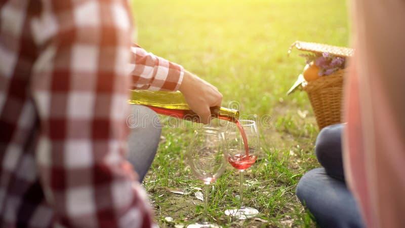 Συνταξιούχος σύζυγος που χύνει το κόκκινο κρασί στα γυαλιά και που θεραπεύει την όμορφη σύζυγο, ημερομηνία στοκ φωτογραφία με δικαίωμα ελεύθερης χρήσης