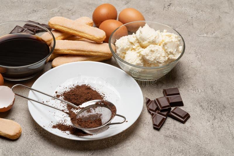 Συστατικά για το tiramisu μαγειρέματος - μπισκότα, mascarpone, κρέμα, ζάχαρη, κακάο, καφές και αυγό μπισκότων Savoiardi στοκ φωτογραφία