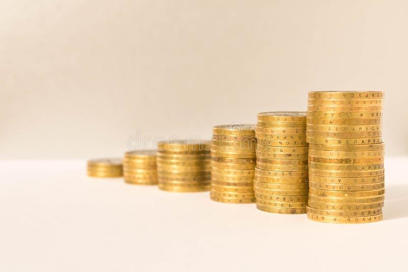 Σωροί των νομισμάτων σε ένα ελαφρύ υπόβαθρο Επιχειρησιακή έννοια και αύξηση του κεφαλαίου στοκ εικόνα