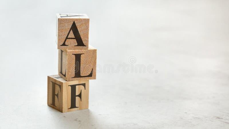 Σωρός με τρεις ξύλινους κύβους - τα γράμματα ALF για ακούνε πάντα πρώτα σε τους, διάστημα για περισσότερο κείμενο/εικόνες στη δεξ στοκ εικόνες