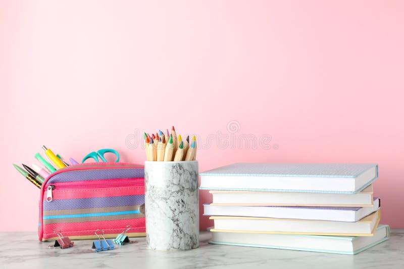 Σωρός των βιβλίων και των χαρτικών hardcover στον πίνακα στο κλίμα χρώματος στοκ εικόνα