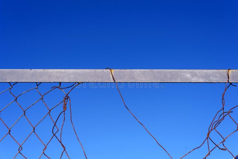 Σπασμένοι φράκτης καλωδίων μετάλλων και υπόβαθρο μπλε ουρανού στοκ φωτογραφίες με δικαίωμα ελεύθερης χρήσης