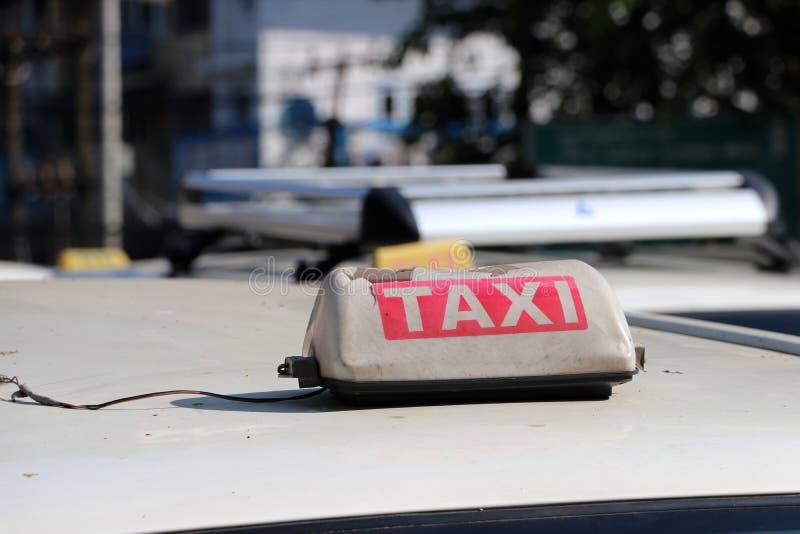 Σπασμένο ελαφρύ σημάδι ταξί ή σημάδι αμαξιών στο μονότονο άσπρο και κόκκινο χρώμα με το άσπρο κείμενο στη στέγη αυτοκινήτων στην  στοκ εικόνες με δικαίωμα ελεύθερης χρήσης