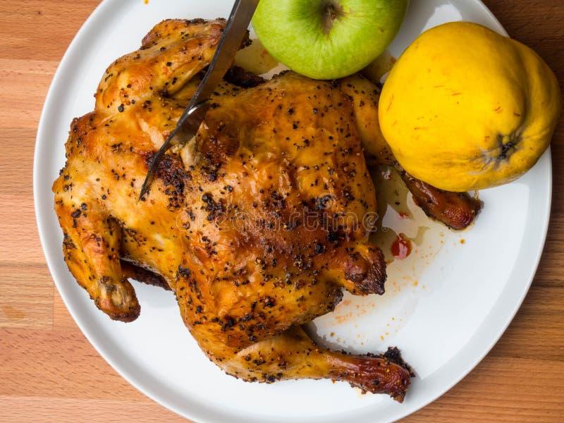 Σπιτικό ολόκληρο ψημένο κοτόπουλο με τα μήλα και το κυδώνι, κόκκινο εορταστικό γεύμα σόγιας souce στοκ εικόνες