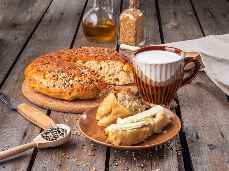 Σπιτικό ψωμί σε μια περικοπή και μια φέτα του τεμαχισμένου ψωμιού που λερώνεται με το βούτυρο και μια κούπα του γάλακτος σε έναν  στοκ φωτογραφία