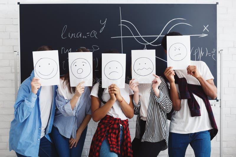 Σπουδαστές που καλύπτουν τα πρόσωπα με τα έγγραφα πέρα από τον πίνακα κιμωλίας στοκ εικόνες με δικαίωμα ελεύθερης χρήσης