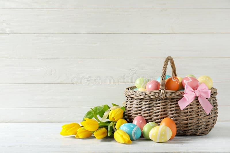 Ψάθινο καλάθι με τα χρωματισμένα αυγά Πάσχας και τα λουλούδια άνοιξη στον πίνακα στοκ φωτογραφία με δικαίωμα ελεύθερης χρήσης
