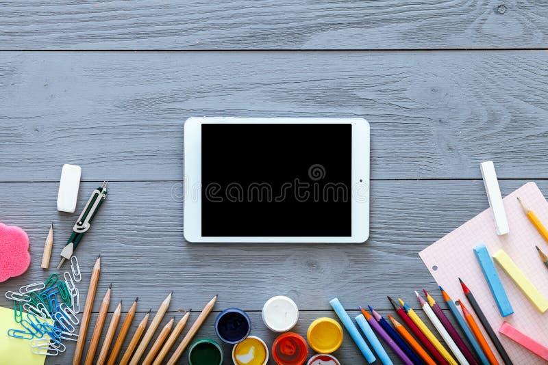 Ψηφιακή ταμπλέτα για την εκπαίδευση, τις σχολικές προμήθειες και τη γραφική πλαστή επάνω κενή κενή μαύρη οθόνη συσκευών στο γκρίζ στοκ φωτογραφία