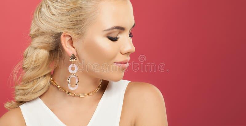 Τέλεια γυναίκα στο χρυσό περιδέραιο αλυσίδων και σκουλαρίκια στο ζωηρόχρωμο ρόδινο κλίμα τοίχων με το διάστημα αντιγράφων στοκ εικόνες με δικαίωμα ελεύθερης χρήσης