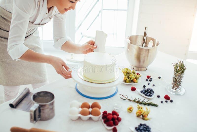 Τέλειος ομαλός αρχιμάγειρας που κρατά μια μεταλλουργική ξύστρα πάγκων agains κάθετα το κέικ στοκ φωτογραφία με δικαίωμα ελεύθερης χρήσης