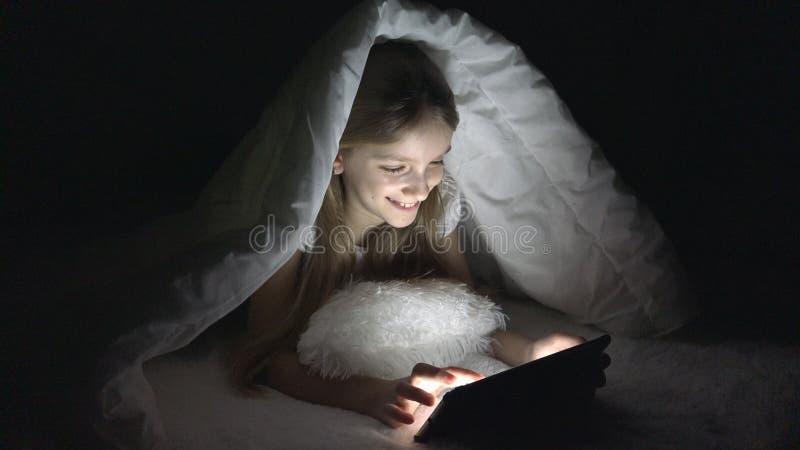 Ταμπλέτα παιχνιδιού παιδιών στη σκοτεινή νύχτα, κορίτσι που κοιτάζει βιαστικά Διαδίκτυο στο κρεβάτι, που δεν κοιμάται στοκ εικόνα