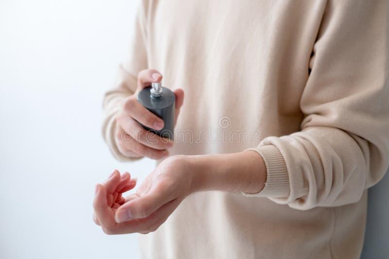 Τα άτομα ψεκάζουν το άρωμα στον καρπό του στοκ φωτογραφία