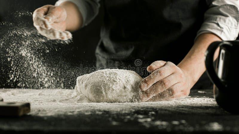 Τα αρσενικά χέρια αρχιμαγείρων ζυμώνουν τη ζύμη με το αλεύρι στον πίνακα κουζινών στοκ φωτογραφίες