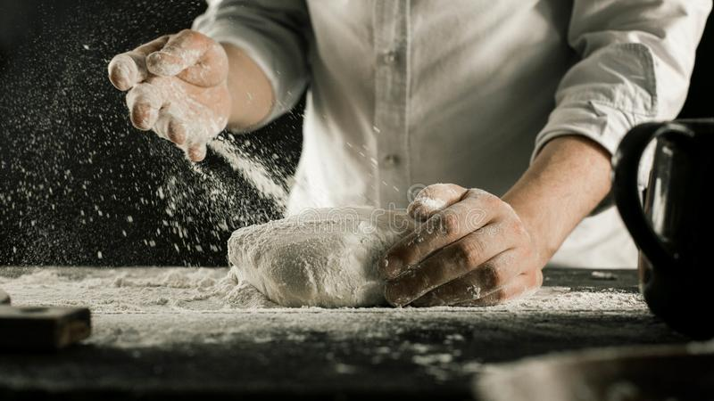 Τα αρσενικά χέρια αρχιμαγείρων ζυμώνουν τη ζύμη με το αλεύρι στον πίνακα κουζινών στοκ εικόνες
