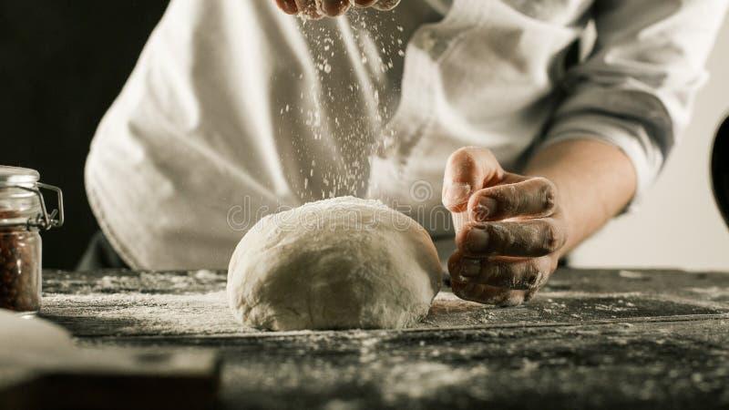 Τα αρσενικά χέρια αρχιμαγείρων ζυμώνουν τη ζύμη με το αλεύρι στον πίνακα κουζινών στοκ φωτογραφίες με δικαίωμα ελεύθερης χρήσης