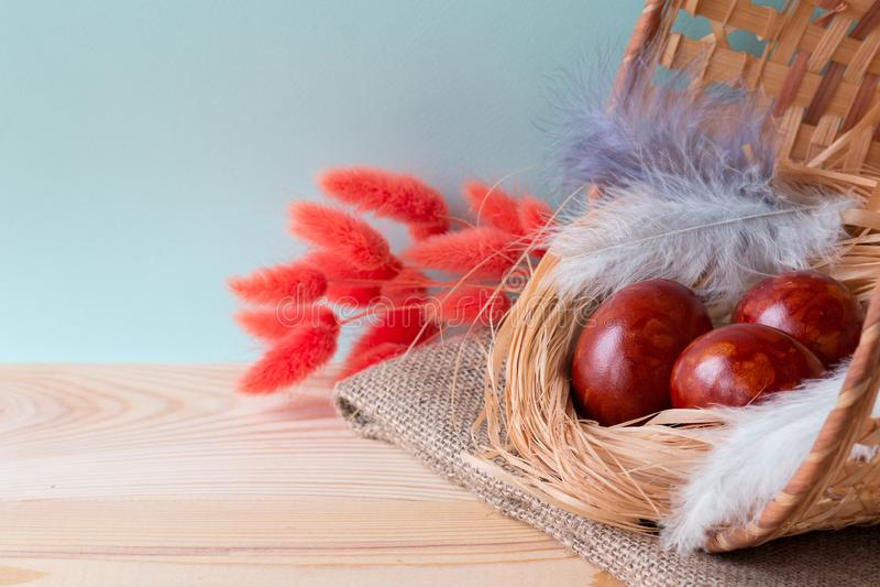 Τα αυγά Πάσχας, χρωμάτισαν μια φλούδα κρεμμυδιών, σε ένα καλάθι σε ένα ξύλινο υπόβαθρο στοκ φωτογραφίες