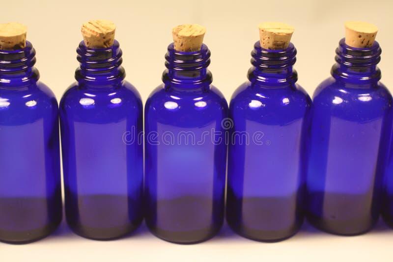 Τα βασιλικά μπλε dropper γυαλιού μπουκάλια με βουλώνουν στοκ εικόνες