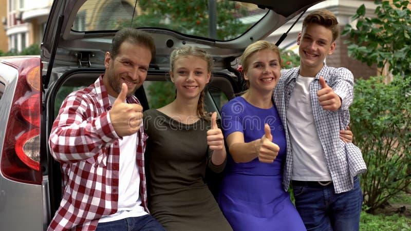 Τα εξαιρετικά ευτυχείς παιδιά και οι γονείς που στέκονται κοντά στον κορμό αυτοκινήτων, παρουσίαση φυλλομετρούν επάνω στοκ φωτογραφίες