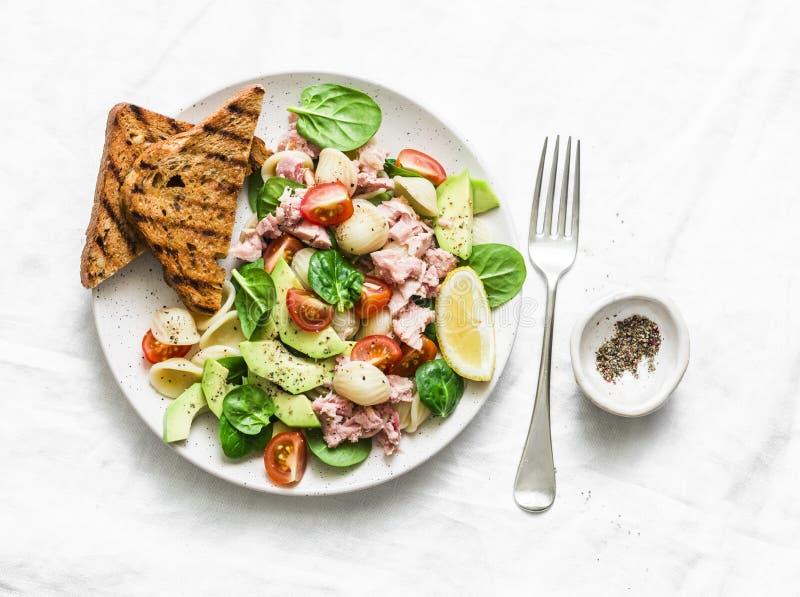 Τα ζυμαρικά Orecchiette, ο τόνος, το αβοκάντο, το σπανάκι, η σαλάτα ντοματών και ολόκληρο το ψωμί σιταριού ψήνουν - εύγευστο υγιέ στοκ εικόνες