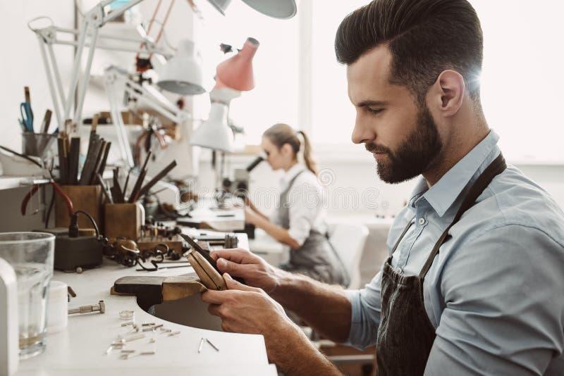 τα θηλυκά αρσενικά μοντέλα ένα εβλάστησαν μαζί δύο εργαζόμενος Η ομάδα Jewelers εργάζεται μαζί στο εργαστήριο κοσμήματος στοκ φωτογραφίες με δικαίωμα ελεύθερης χρήσης